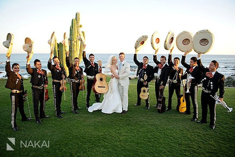 A band posing at a Cabo wedding with the bride and groom